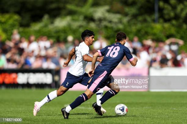 Dilan Markanday of Tottenham Hotspur runs with the ball past Lewis White of Dulwich Hamlet during the PreSeason Friendly match between Dulwich Hamlet...