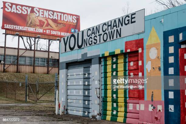 YOUNGSTOWN OHIO MARCH 2 A dilapidated building with a positive message in front of a billboard for an adult store in Youngstown Ohio on March 2 2017...