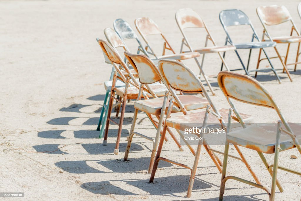 Dilapidated chairs arranged in circle in dirt field : Foto stock