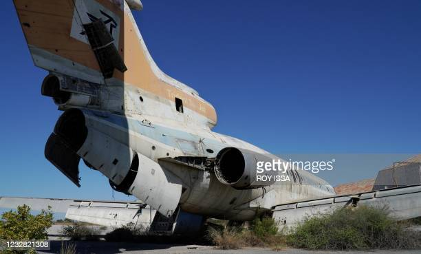 Dilapidated Cyprus Airways Trident 2E aircraft, with its nose and doors missing and its sides dotted with bullet holes, sits on the tarmac of the...
