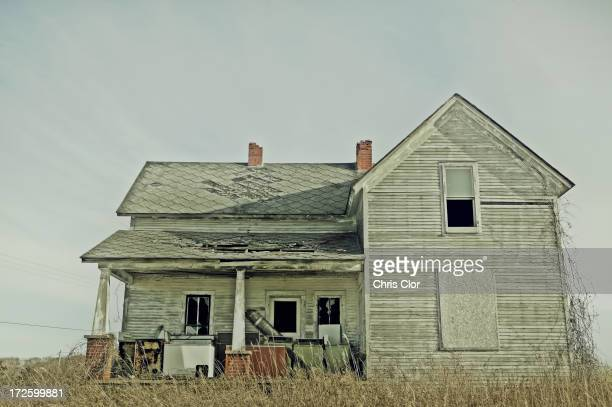 Dilapidated house in dry field