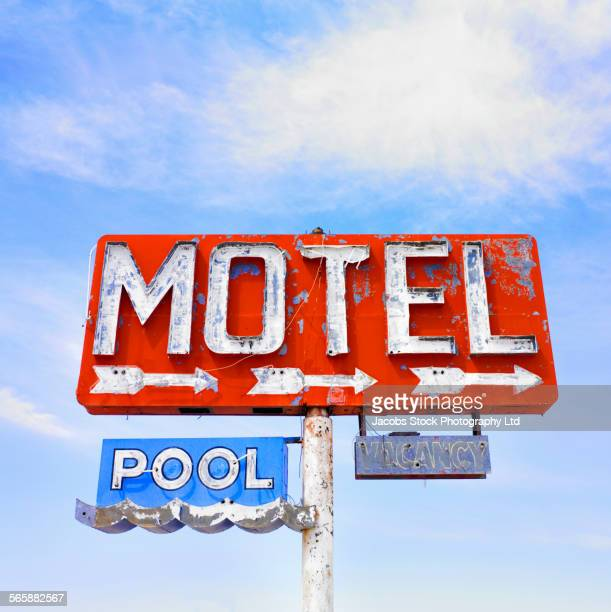 Dilapidated motel neon sign under blue sky