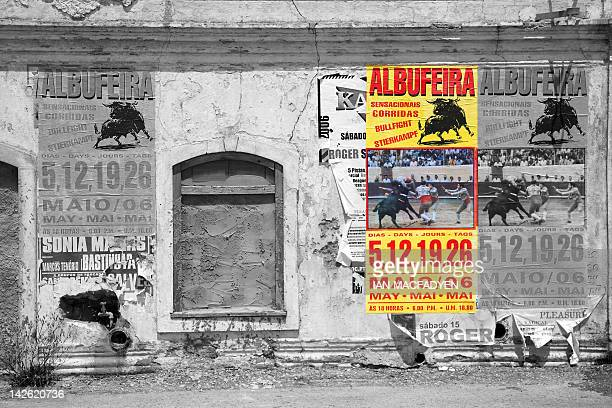 Dilapidated shop frontage adorned with advertising hoardings depicts a forthcoming bullfight.