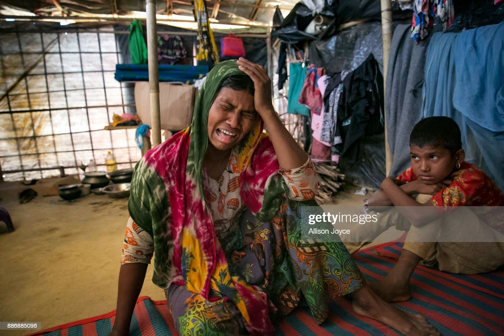 COX'S BAZAR, BANGLADESH - DECEMBER 03: Dildar Begum, 30, becomes emotional while her 10 year old daughter, Nurkalima, looks on, on December 3, 2017 in Cox's Bazar, Bangladesh. She fled to Bangladesh shortly after the August 25th attack from Tula Toli village in Myanmar. She says that one day the military came and opened fired on her village and stormed into her house. They took her husband out of the house and to the riverbank and shot him. Then they came back into her house and grabbed her baby from her arms and stabbed him in the head. They killed another one of her children by cutting his throat, and another by beating her over the head with a rifle. 2 military held her arms while another raped her. They then beat her and she pretended to be dead. When they left, they set her house on fire. Her 10 year old daughter, Nurkalima, was severely injured when the military beat her over the head with the blades of machetes, but she helped her mom crawl past the burning bodies of her children and out of the burning house. For 5 days she hid in the hills and when the military left, she went back to Tula Toli on her way to the Bangladesh border. All that was left of her village was smoke and ask where houses used to be. There were bodies everywhere, so many that they were uncountable. She came across some men who carried her for two days to the border, where they were able to cross into Bangladesh by boat. 'I don't see any future for me here in Bangladesh. My husband is dead, who will earn money for me and my daughter? I want justice. My kids were killed, I want justice for them.' she says. Human Rights groups have reported of widespread rape and sexual assault on Rohingya women and girls by Burmese security forces during the violence in Myanmar's Rakhine State.