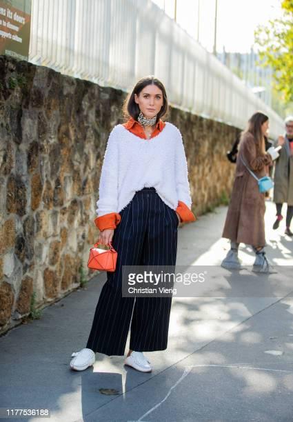 Diletta Bonaiuti is seen wearing orange mini bag, striped navy pants, white knit outside Loewe during Paris Fashion Week Womenswear Spring Summer...