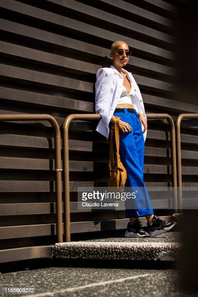 Diletta Natoli, wearing a white crop top, white shirt, blue pants, black sneakers and yellow bag, is seen during Pitti Immagine Uomo 96 on June 12,...