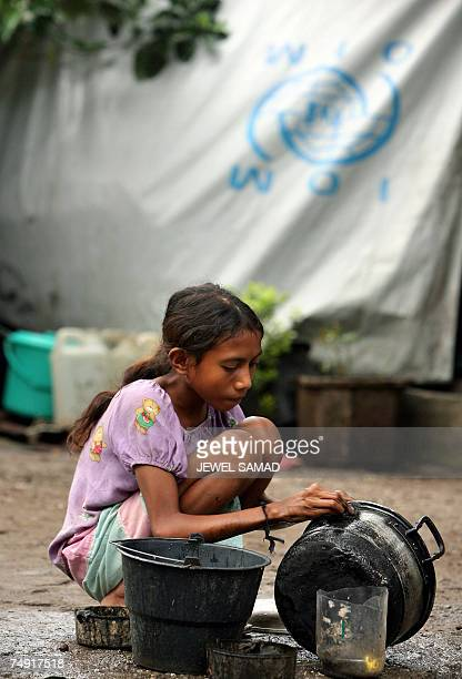 Girl washes dishes near her tent at a refugee camp in Dili, 26 June 2007. Some 25,000 refugees, who are seeking shelter in predominantly Catholic...