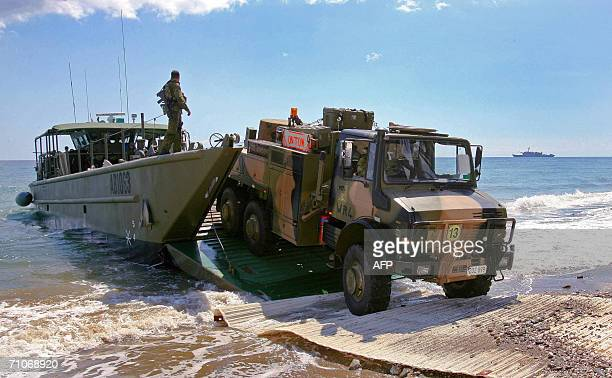 An Australian army truck is unloaded from a landing craft as hundreds of additional troops landed in Dili 28 May 2006 to boost an international...