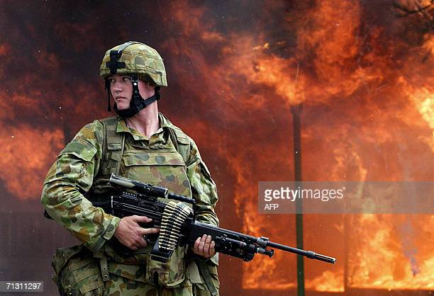 An Australian soldier stands alert next to a burning house set on fire by unknown gang members in Dili 28 June 2006 Stonethrowing youths attacked...