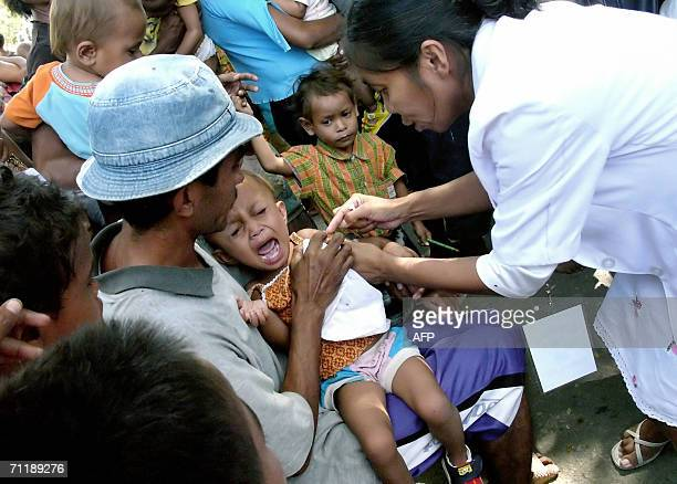 An East Timorese health worker vaccinates a child against measle at a refugee camp in Dili 13 June 2006 Opponents of East Timor's Prime Minister Mari...