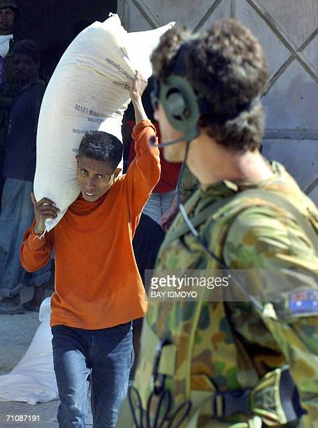 An East Timorese man caries a sack of free rice under the watchful eye of an Australian soldier as unrest continues for another day in the East Timor...