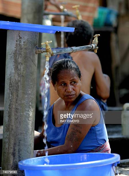 An East Timorese woman fills her plastic bucket with water at a refugee camp in Dili 05 May 2007 East Timorese head to the polls Wednesday for the...