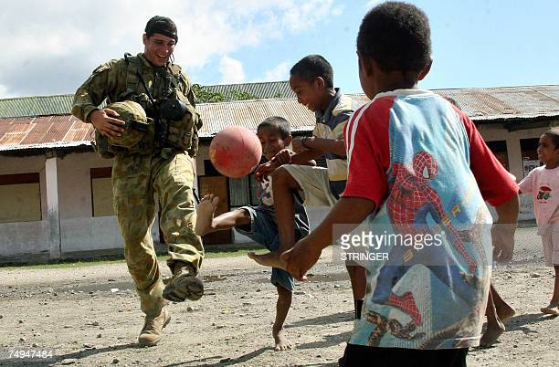 An international peacekeeping soldier from Australia plays football with children at a refugee camp Dili 29 June 2007 East Timor's voters head to...
