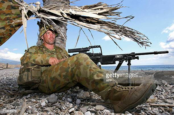 Australian soldier gunner Andrew Cox keeps guard as landing craft discharge their cargo of equipment and soldiers as hundreds of additional...