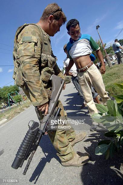 Australian soldiers on patrol check residents for weapons during a clash between gangs near the airport in Dili 05 June 2006 Australian troops fired...