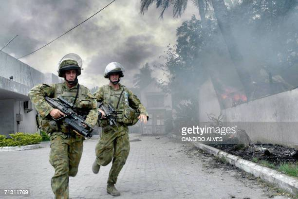 Australian soldiers run to stop a mob from burning a house in Dili 28 June 2006 Stonethrowing youths attacked refugee camps in East Timor raising...