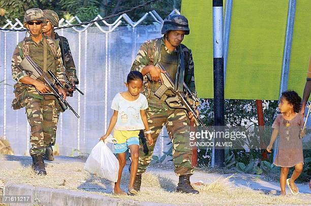 East Timorese children look at Malaysian soldiers patrolling along a street in Dili 09 August 2006 Malaysia is planning to pull out most of its 200...