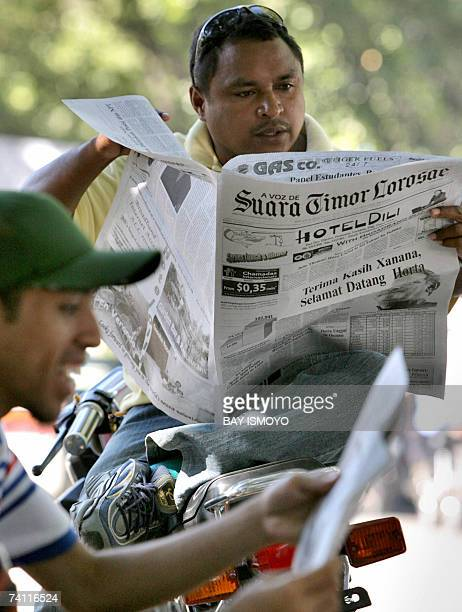 East Timorese youths read a newspaper featuring a headline reading Thank you Xanana Welcome Horta in Dili 10 May 2007 a day after the presidential...