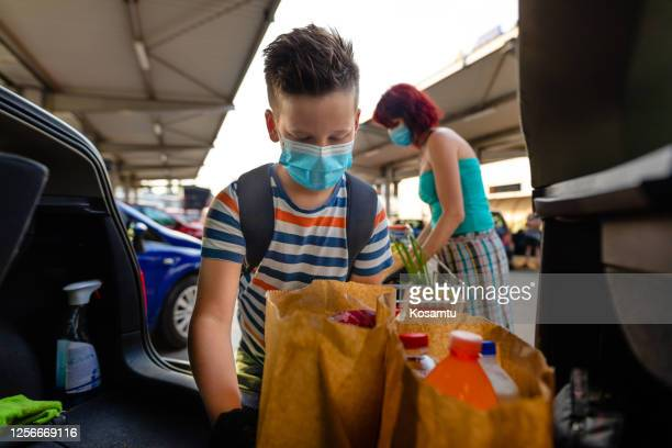 diligent 9 years old son helping his mother to pack groceries into car trunk after shopping - 8 9 years stock pictures, royalty-free photos & images