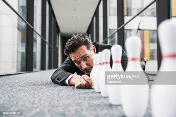 diligent manager lying on the floor in office passageway adjusting pins - excesso imagens e fotografias de stock