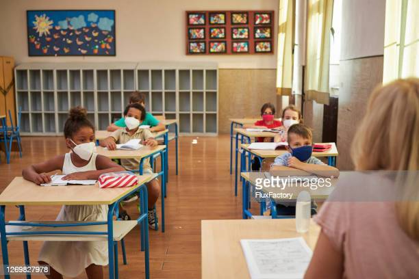 diligent students carefully following lecture during teacher speak at their first day at school during corona virus pandemic - attending stock pictures, royalty-free photos & images
