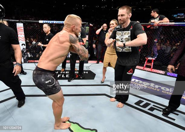 Dillashaw celebrates with coach Duane Ludwig after his knockout victory over Cody Garbrandt in their UFC bantamweight championship fight during the...