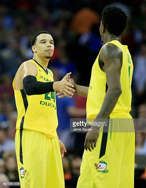 Dillon Brooks and Jordan Bell of the Oregon Ducks celebrate their 79 to 73 win over the Oklahoma State Cowboys during the second round of the 2015...