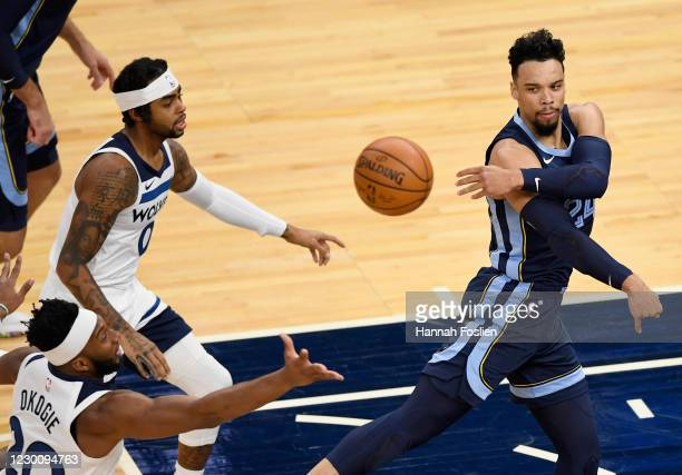 Dillon Brooks of the Memphis Grizzlies passes the ball against Josh Okogie and D'Angelo Russell of the Minnesota Timberwolves during the first...