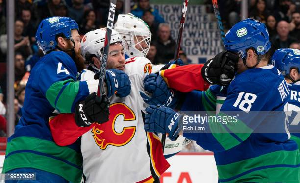 Dillon Dube of the Calgary Flames gets a hand in the face of Jake Virtanen of the Vancouver Canucks while held by Jordie Benn during NHL action at...
