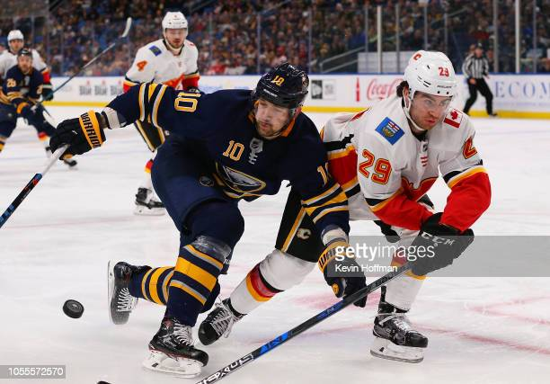 Dillon Dube of the Calgary Flames knocks the puck away from Patrik Berglund of the Buffalo Sabres during the second period at the KeyBank Center on...