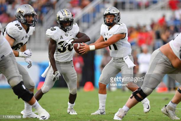 Dillon Gabriel of the UCF Knights hands the ball off to Greg McCrae the first half against the Florida Atlantic Owls at FAU Stadium on September 07...