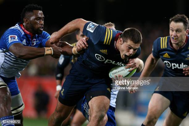 Dillon Hunt of the Highlanders fends off Siya Kolisi of the Stormers during the round 10 Super Rugby match between the Highlanders and the Stormers...