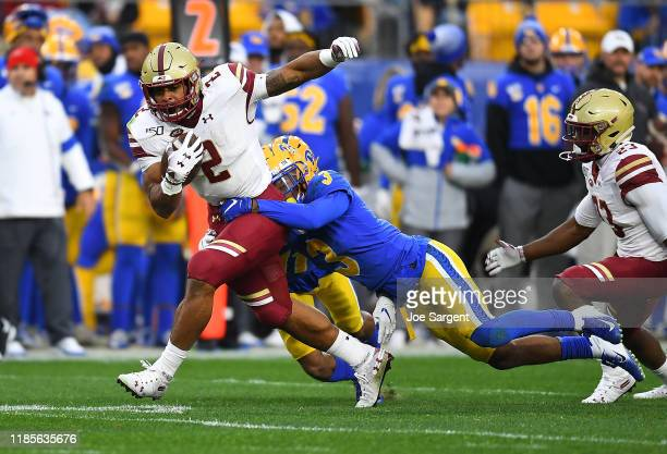 Dillon of the Boston College Eagles gets tackled by Damar Hamlin of the Pittsburgh Panthers during the first quarter at Heinz Field on November 30...
