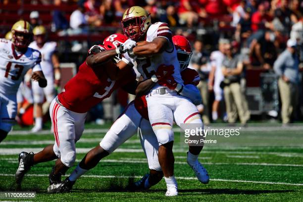 Dillon of the Boston College Eagles is tackled by Olakunle Fatukasi of the Rutgers Scarlet Knights and Rashawn Battle during the third quarter at SHI...