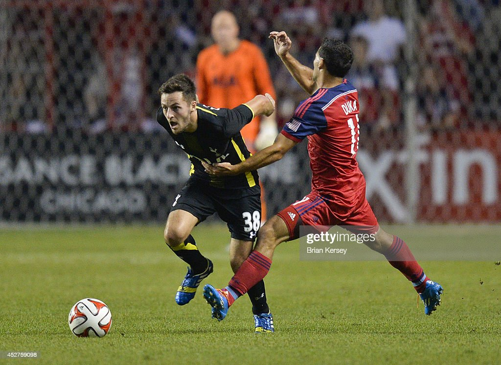 Dilly Duka #11 of Chicago Fire (R) trips Ryan Mason #38 of Tottenham Hotspur during the second half at Toyota Park on July 26, 2014 in Bridgeview, Illinois. Tottenham Hotspur defeated the Fire 2-0.