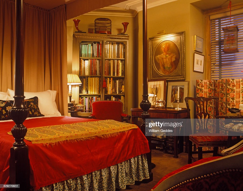 Dim Red And Gold Bedroom With Wooden Canopy Bed And Bookshelf : Stock Photo
