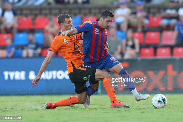 Dimi Petratos of the Newcastle Jets contests the ball with Daniel Bowles of Brisbane Roar during the round 12 A-League match between the Newcastle...