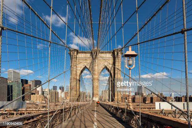 diminishing perspective of brooklyn bridge against blue sky in new york city, usa - brooklyn bridge stock pictures, royalty-free photos & images