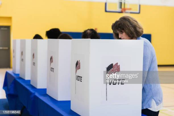diminishing perspective of diverse people at voting booths - voting booth stock pictures, royalty-free photos & images