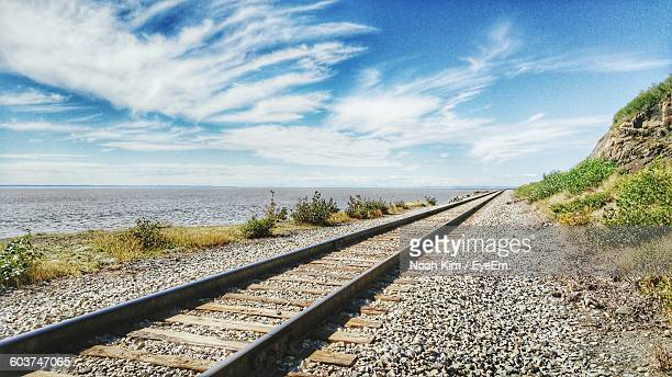 diminishing view of railroad tracks by sea against sky - tramway stock pictures, royalty-free photos & images
