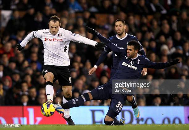 Dimitar Berbatov of Fulham battles with Sandro of Tottenham during the Barclays Premier League match between Fulham and Tottenham Hotspur at Craven...