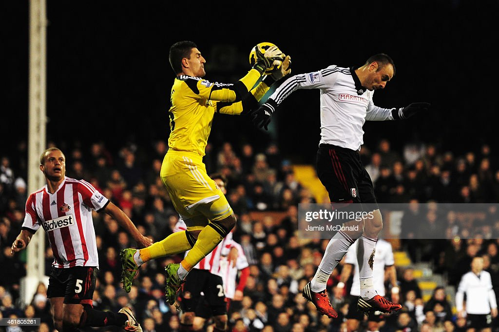 Dimitar Berbatov (R) of Fulham challenges Vito Mannone the Sunderland goalkeeper during the Barclays Premier League match between Fulham and Sunderland at Craven Cottage on January 11, 2014 in London, England.