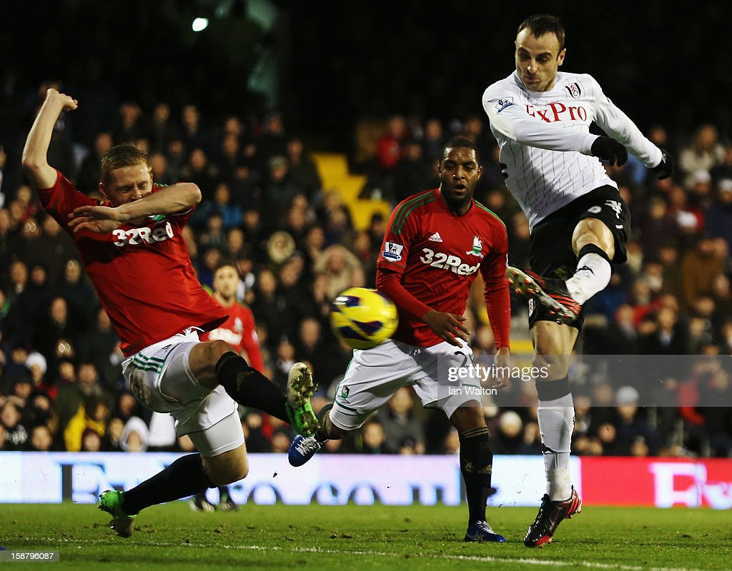 Dimitar Berbatov (R) of Fulham shoots on goal as Garry Monk (L) of Swansea City tries to block the shot during the Barclays Premier League match between Fulham and Swansea City at Craven Cottage on December 29, 2012 in London, England.