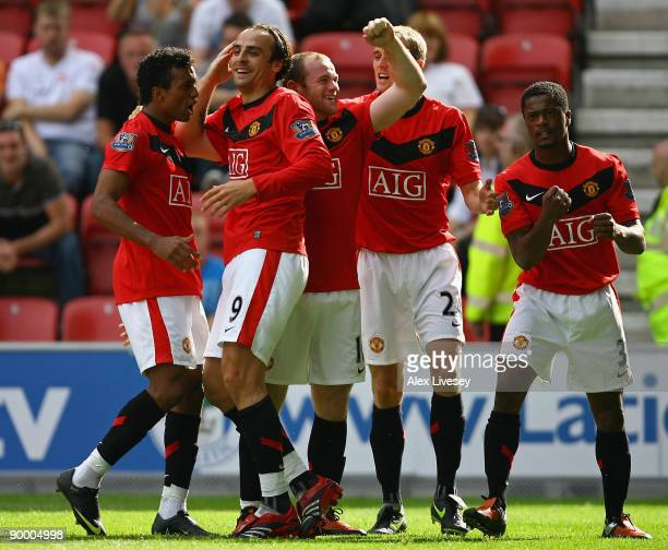 Dimitar Berbatov of Manchester United celebrates with his team mates after scoring the second goal during the Barclays Premier League match between...