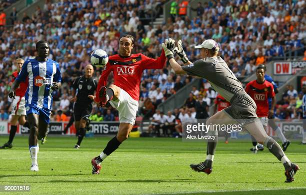 Dimitar Berbatov of Manchester United chips the ball over Chris Kirkland of Wigan Athletic on his way to scoring the second goal during the Barclays...