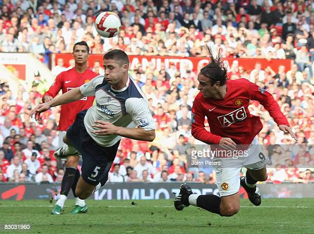 Dimitar Berbatov of Manchester United clashes with Gary Cahill of Bolton Wanderers during the FA Premier League match between Manchester United and...