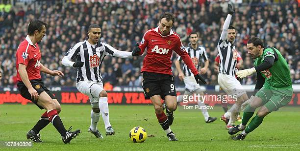 Dimitar Berbatov of Manchester United clashes with Jerome Thomas Paul Scharner and Scott Carson of West Bromwich Albion during the Barclays Premier...