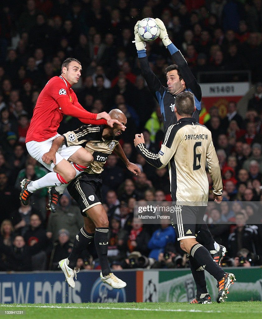 Dimitar Berbatov of Manchester United clashes with Luisao and Artur of Benfica during the UEFA Champions League Group C match between Manchester United and Benfica at Old Trafford on November 22, 2011 in Manchester, England.