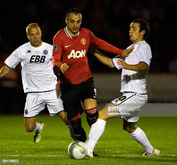 Dimitar Berbatov of Manchester United gets past Luke Gutteridge and Danny Hylton of Aldershot Town