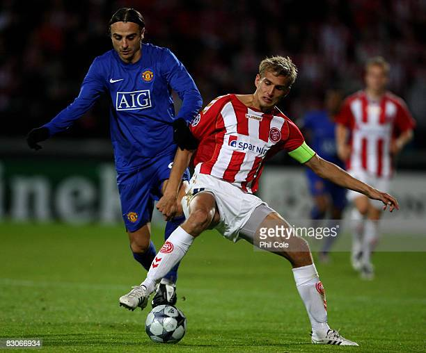 Dimitar Berbatov of Manchester United gets tackled by Thomas Augustinussen of Aalborg during the UEFA Champions League Group E match between Aalborg...